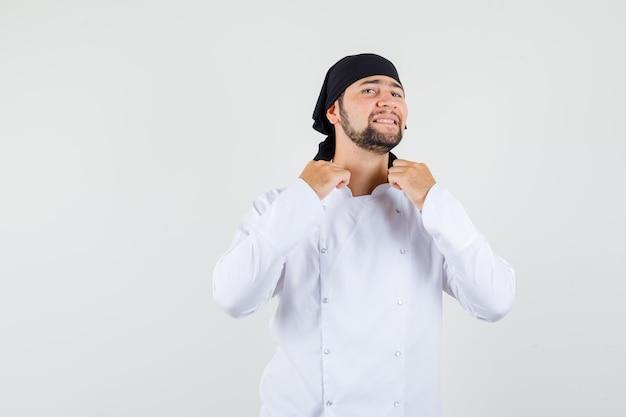 白い制服を着て首輪を引っ張る男性シェフ、エレガントな正面図。
