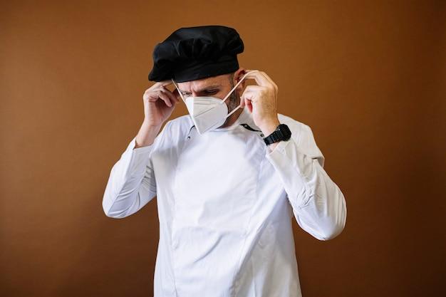 Мужчина-повар надевает маску