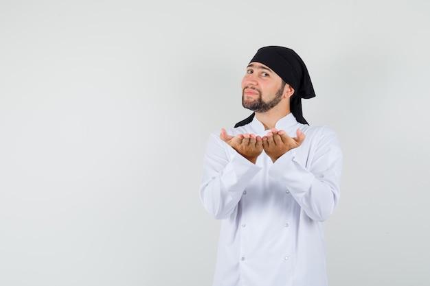 Lo chef maschio alza le mani aperte come se tenesse qualcosa in uniforme bianca e sembra allegro, vista frontale.
