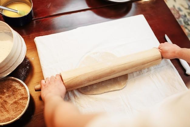 男性シェフが麺棒、上面図、木製キッチンテーブルで生地を伸ばす