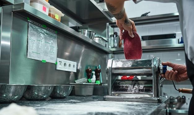 Male chef rolling a knead through pasta machine while working in restaurant kitchen