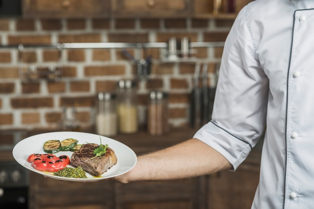 Male chef's hand holding delicious beef steak dish with roasted veggies