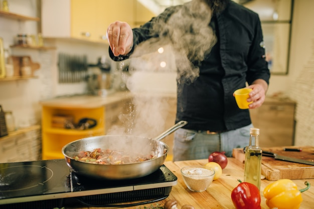 Шеф-повар посолил мясо с овощами на сковороде на кухне. человек готовит говядину на столовой электрической плите