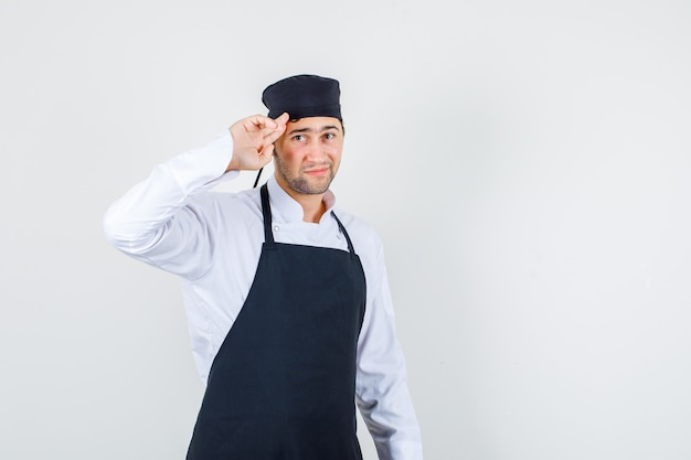 Male chef saluting with two fingers on temples in uniform, apron and looking cute. front view.