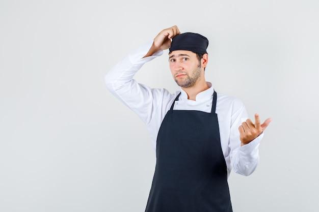 Мужчина-шеф-повар почесывает голову жестом пистолета в униформе, фартуке и задумчиво выглядит. передний план.
