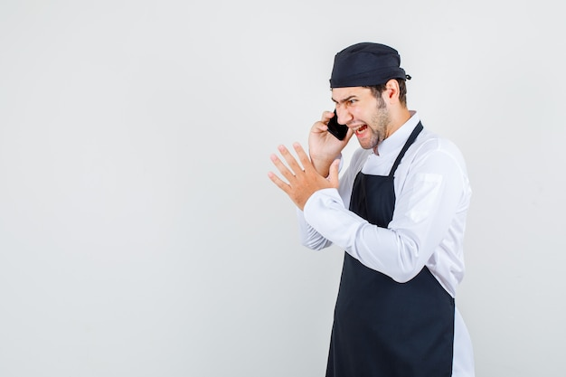Male chef shouting while talking on smartphone in uniform, apron and looking furious , front view.