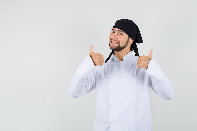 Male chef showing double thumbs up in white uniform and looking positive , front view.