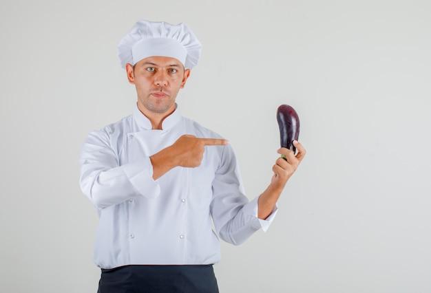 유니폼, 앞치마와 모자에 그의 손에 가지를 보여주는 남자 요리사