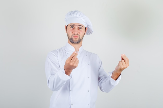 Male chef showing gesture with hands in white uniform and looking confused