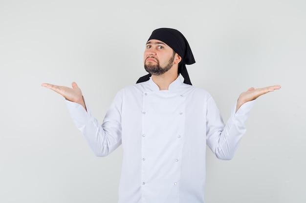 Шеф-повар-мужчина показывает беспомощный жест в белой форме и выглядит смущенным. передний план.