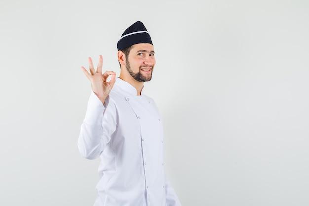 Cuoco unico maschio che mostra gesto ok in uniforme bianca e sembra soddisfatto. vista frontale.
