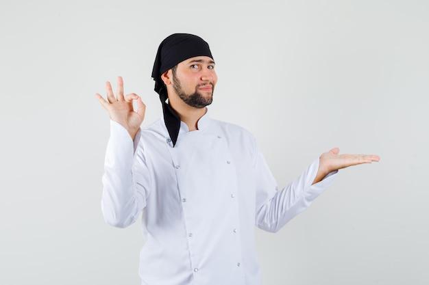 手のひらでokサインを見せている男性シェフが白い制服を着て脇に広がり、喜んでいるように見えます。正面図。