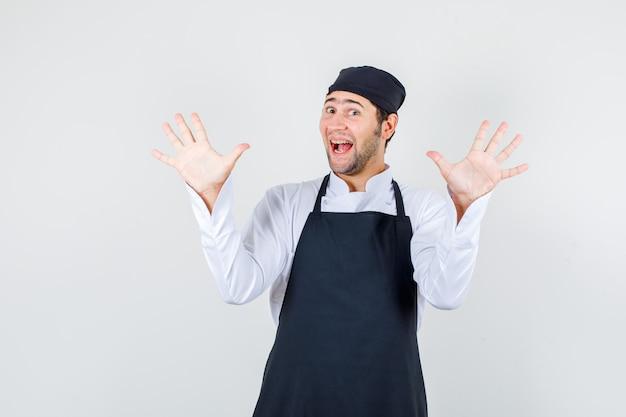 Cuoco unico maschio che mostra i palmi in su in uniforme, grembiule e sembra energico, vista frontale.