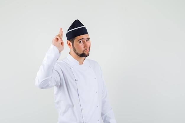 남자 요리사는 흰색 제복을 입고 용감해 보이는 권총 제스처를 보여줍니다. 전면보기.