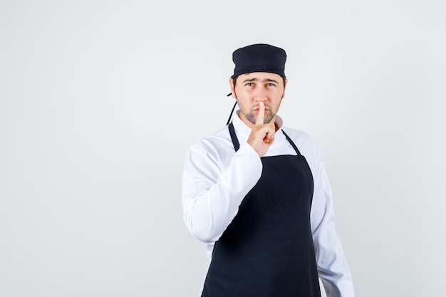 Male chef showing silence gesture in uniform, apron and looking careful , front view.