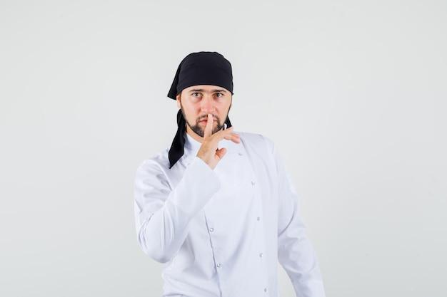 Cuoco unico maschio che mostra gesto di silenzio in uniforme bianca e guarda attento. vista frontale.