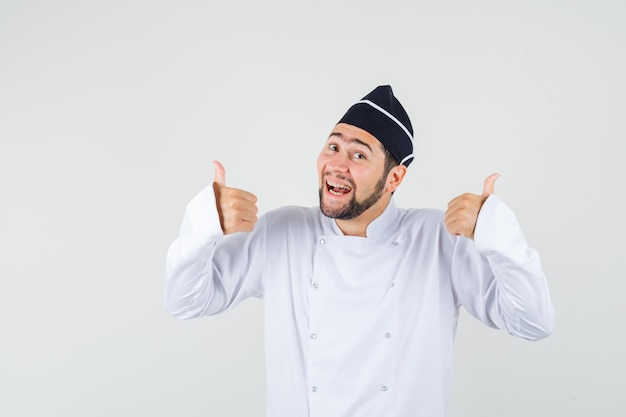 Male chef showing thumb up while smiling in white uniform and looking pleased , front view.