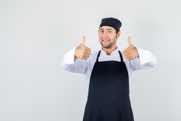 制服、エプロンで親指を立てて幸せそうに見える男性シェフ。正面図。