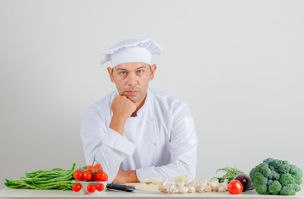 Male chef sitting and looking at camera in uniform and hat in kitchen