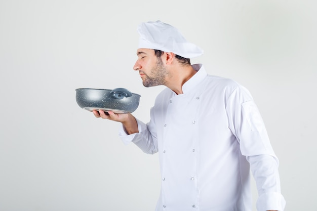 Male chef smelling meal in pan in white uniform