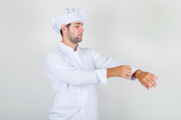 Chef maschio che si liscia la giacca in uniforme bianca e sembra in ordine.