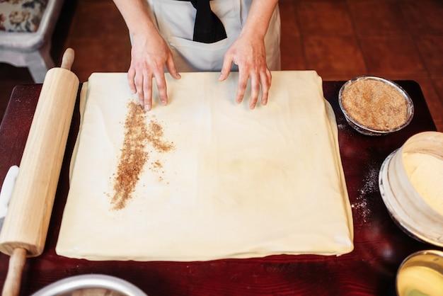 男性シェフが生地にシナモンを振りかける、リンゴのシュトルーデル料理。自家製の甘いデザート、おいしいパイの準備プロセス
