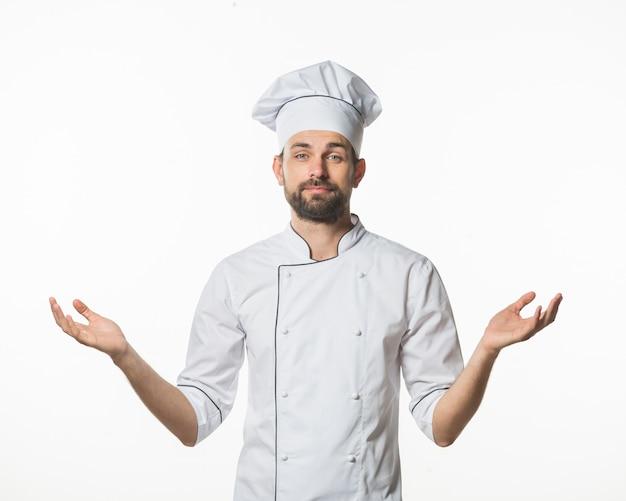 Male chef standing against white background shrugging