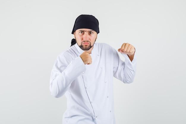 Cuoco unico maschio che sta nella posa del pugile in uniforme bianca e che sembra nervoso. vista frontale.