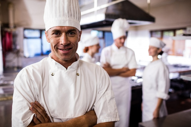 Male chef standing with arms crossed while coworker interacting with each other in kitchen