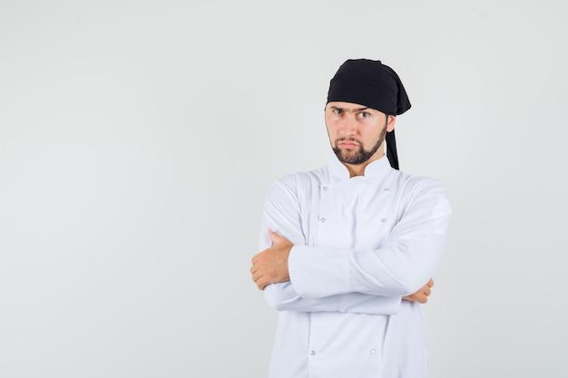 白い制服を着て腕を組んで立って物思いにふける男性シェフ。正面図。