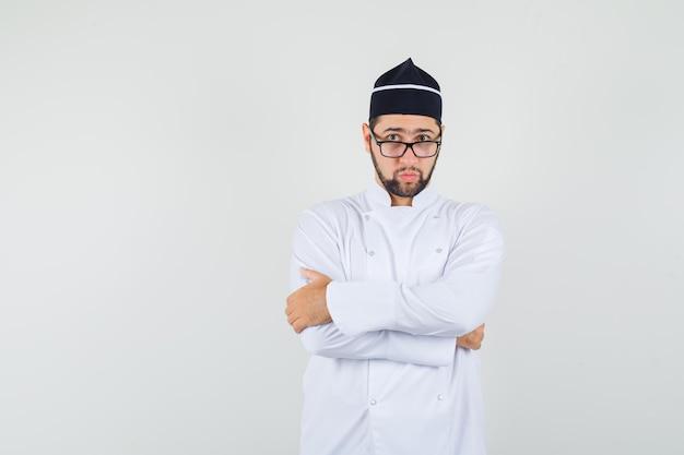 Chef maschio in piedi con le braccia incrociate in uniforme bianca, occhiali e dall'aspetto serio. vista frontale.