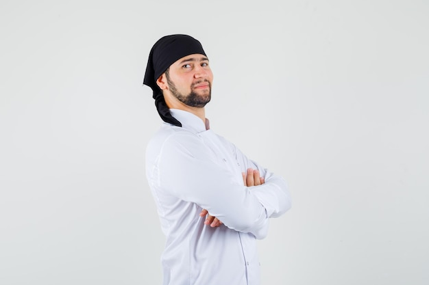 Chef maschio in piedi con le braccia incrociate in uniforme bianca e dall'aspetto fiducioso. vista frontale.