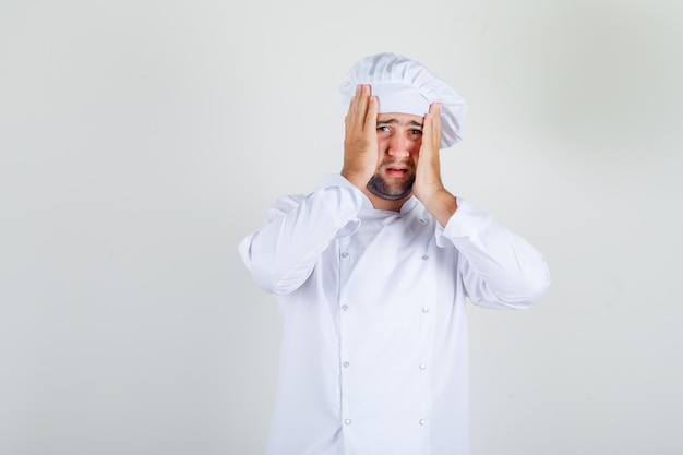 Male chef standing with head in hands in white uniform and looking confused.