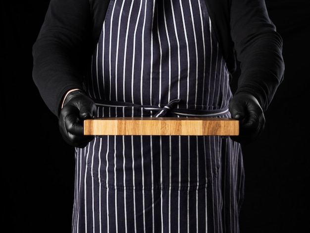 Male chef in a striped blue apron and black clothes stands against a black background and holds in his hand a rectangular wooden kitchen chopping board, close up