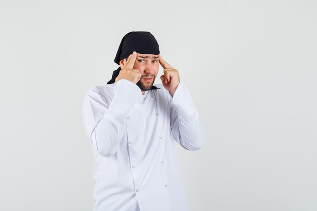 백인 제복을 입고 만성 편두통을 앓고 있는 남성 요리사는 지쳐 보이는 전면 전망입니다.