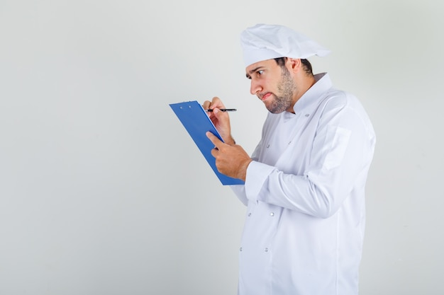 Male chef taking notes on clipboard in white uniform and looking busy
