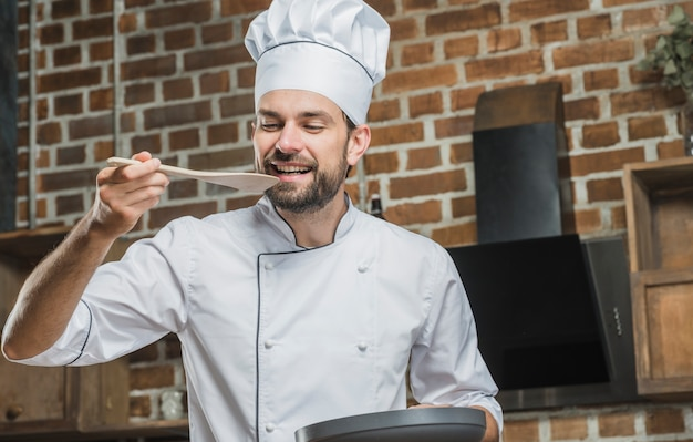 Male chef tasting food on wooden spatula