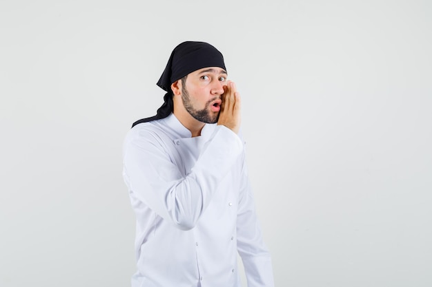 남자 요리사는 흰색 제복을 입고 비밀을 말하고 호기심을 보입니다. 전면보기.