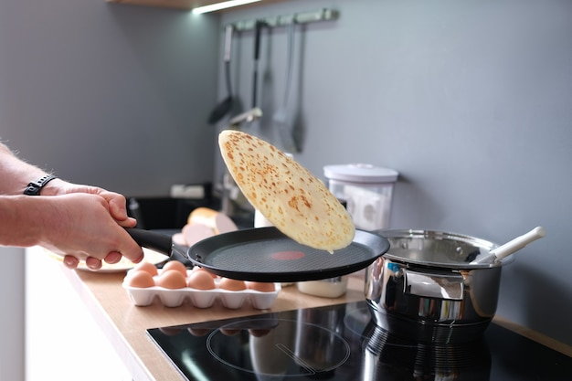 Male chef tossing pancake in frying pan in kitchen closeup