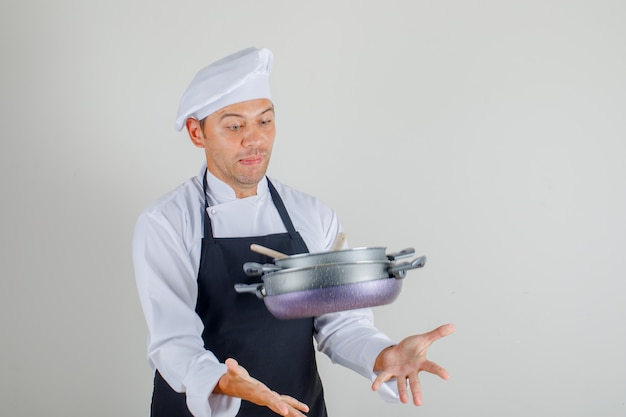 Male chef trying to catch flying pan set in uniform, apron and hat and looking scared