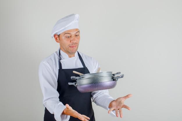 Мужской шеф-повар пытается поймать летающую кастрюлю в форме, фартуке и шляпе и выглядит испуганным