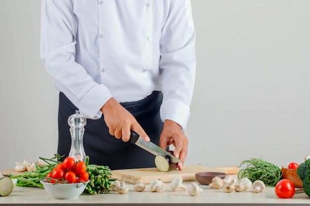 Male chef in uniform and apron chopping eggplant on wooden board in kitchen