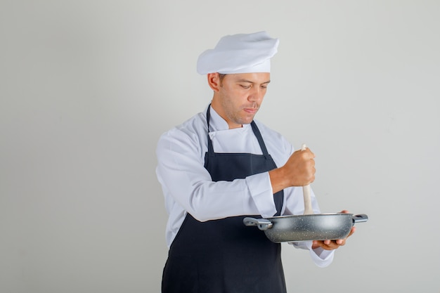 Male chef in uniform, apron and hat preparing meal using pan and spoon