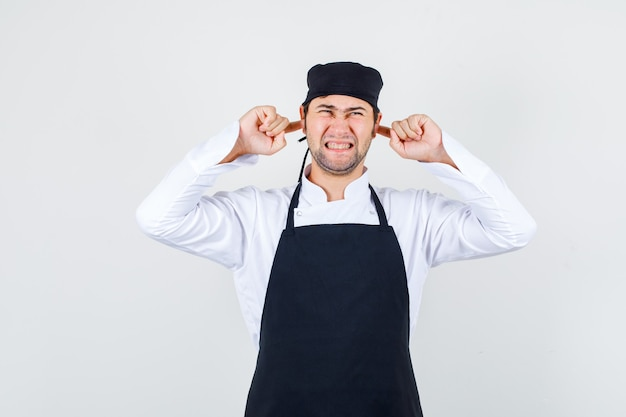 Male chef in uniform, apron plugging ears with fingers and looking annoyed , front view.