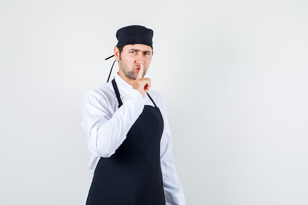 Chef maschio in uniforme, grembiule che mostra gesto di silenzio mentre accigliato, vista frontale.