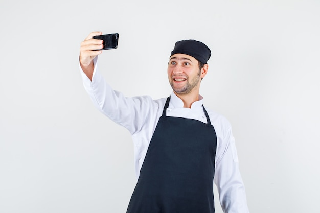 Chef maschio in uniforme, grembiule prendendo selfie su smartphone e guardando allegro, vista frontale.