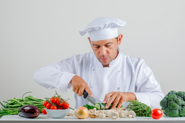 Male chef in uniform and hat sitting and cutting cucumber in kitchen