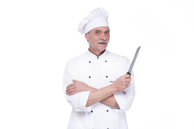 Male chef in uniform holding metal knife while staying on white wall