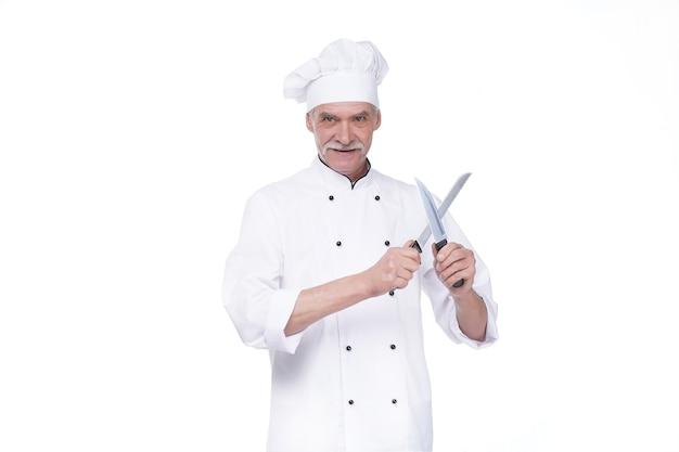Cuoco unico maschio in uniforme che tiene due coltelli di metallo mentre rimane sul muro bianco
