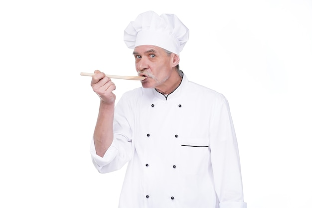 Male chef in uniform holding wooden spoon on white wall
